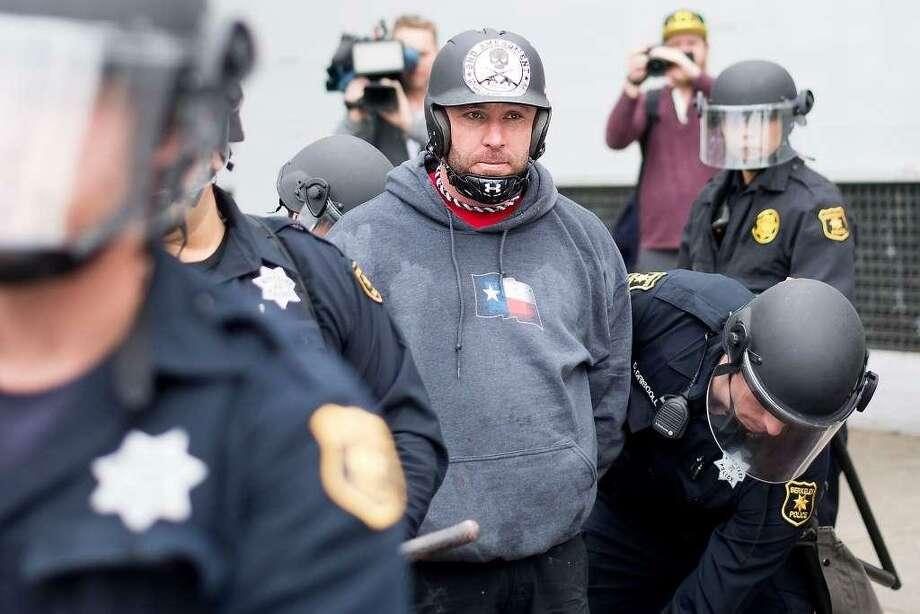 Police officers detain demonstrator, Kyle Chapman in Berkeley, Calif., on Saturday, March 4, 2017.