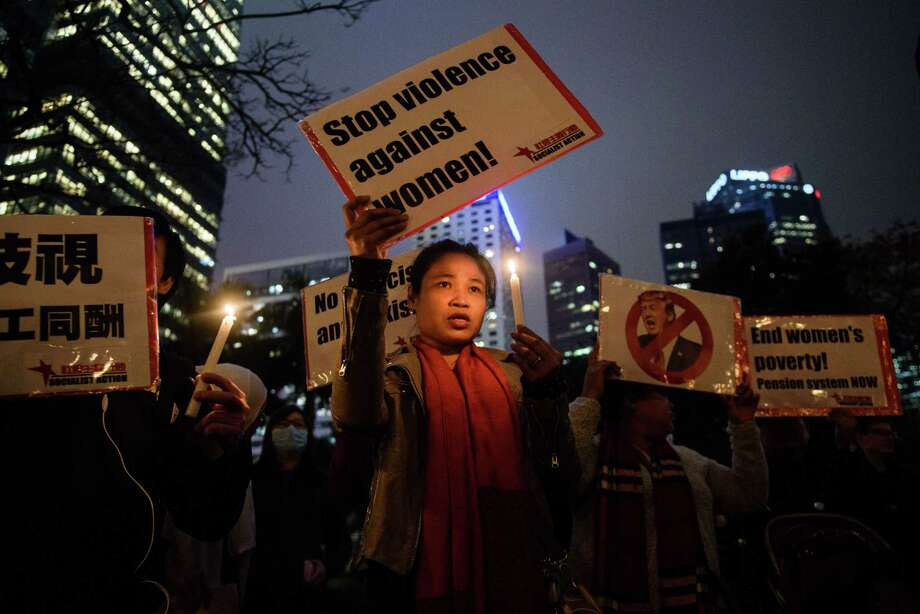 Participants hold candles and placards against US President Donald Trump during a vigil to mark International Women's Day (IWD) in Hong Kong on March 8, 2017. / AFP PHOTO / Anthony WALLACE Photo: ANTHONY WALLACE, AFP/Getty Images / This content is subject to copyright.