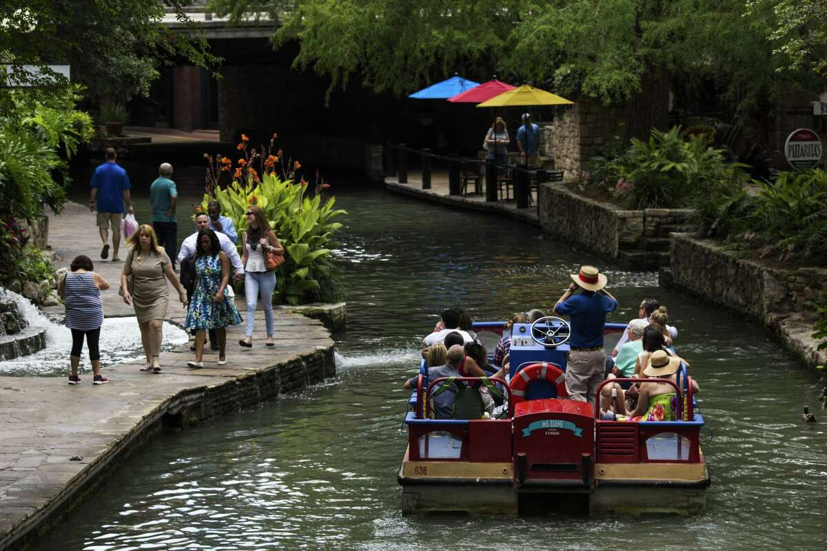 Tourists walk the stone pathways on the River Walk as a boat tour guide with Rio San Antonio Cruises drives his group down the San Antonio River in downtown San Antonio on Friday, June 10, 2016.
