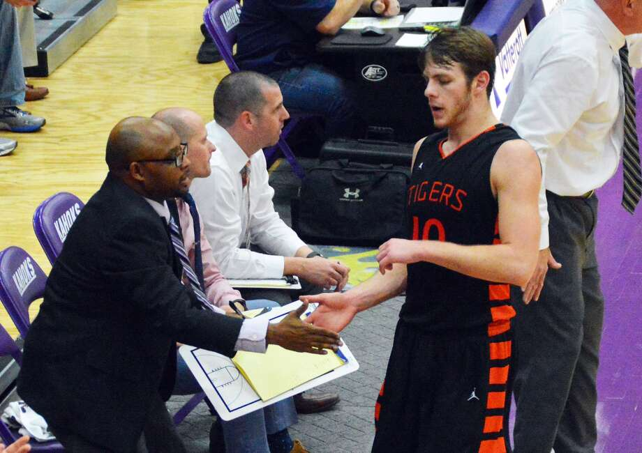 Edwardsville senior Nathan Kolesa, right, is congratulated by the coaching staff after leaving the court late in the fourth quarter of Tuesday's sectional semifinal game against Belleville West in Collinsville.