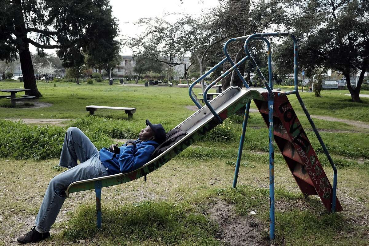 Vickie Wiggins of Richmond listens to music on her phone while relaxing at People's Park before her work shift at a local cafeteria, in Berkeley, CA, on Tuesday March 7, 2017,