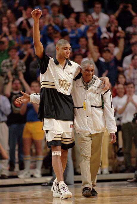 ** FILE ** Wake Forest All-American center Tim Duncan and his dad, William, are introduced to the crowd, at Joel Coliseum, in Winston-Salem, N.C., before the start of a game against Georgia Tech, in this February 25, 1997 photo. Duncan's jersey was being retired after the game. Tim Duncan will miss Game 4 of the San Antonio Spurs' playoff series Wednesday night, May 1, 2002 against the Seattle SuperSonics after his father died earlier this week. (AP Photo/Bob Jordan) Photo: BOB JORDAN, STF / AP / AP