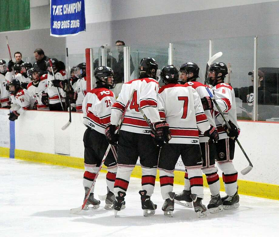 New Canaan's Tyler Hill (7) is congratulated by teammates after scoring a second-period goal during Wednesday's 4-0 win over Greenwich in the Division I boys ice hockey playoff at Darien Ice Rink. Photo: Bob Luckey Jr. / Hearst Connecticut Media / Greenwich Time