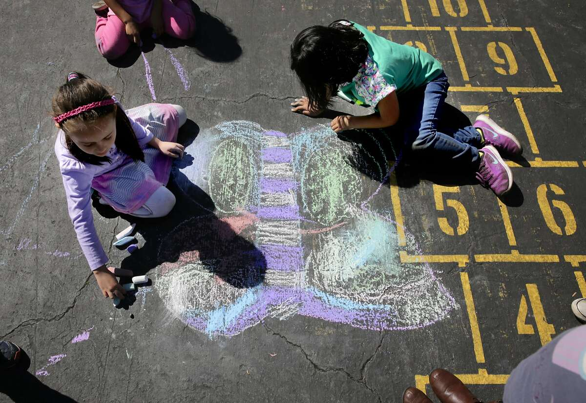 Alina Barascout, (left) and Molly Cho who are in kindergarten draw playground art during recess at Bay Farm Elementary School on Wed. March 8, 2017, in Alameda, Ca.
