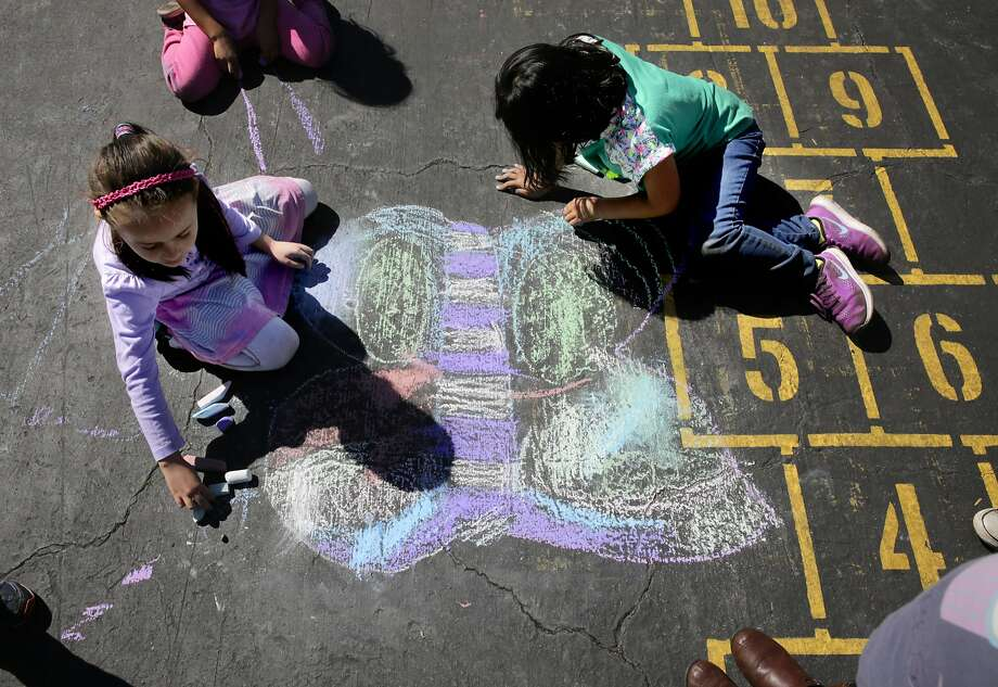 Alina Barascout (left) and Molly Cho draw playground art during recess at Bay Farm Elementary School in Alameda. Photo: Michael Macor, The Chronicle