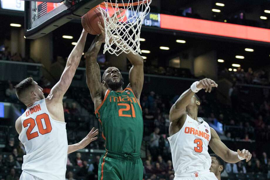 Miami forward Kamari Murphy (21) goes to the basket past Syracuse forward Tyler Lydon (20) and guard Andrew White III (3) during the first half of an NCAA college basketball game in the Atlantic Coast Conference tournament, Wednesday, March 8, 2017, in New York. (AP Photo/Mary Altaffer) ORG XMIT: NYMA102 Photo: Mary Altaffer / Copyright 2017 The Associated Press. All rights reserved.