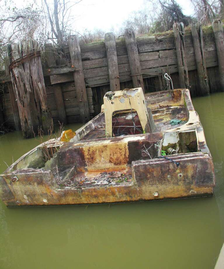 Abandoned boats, such as this derelict left in a side channel of the lower Trinity River, are hazards to boaters and the environment. The Texas General Land Office's Vessel Turn-In Program offers a way boat owners can, at no cost to them, properly dispose of unwanted vessels. Photo: Shannon Tompkins