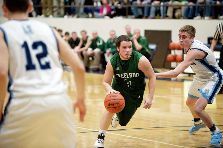 BRITTNEY LOHMILLER | blohmiller@mdn.net Freeland's Zac Anderson  dribbles around Meridian's Brett Bohn in the first half of Wednesday's Class B district semifinal at Bay City John Glenn. Anderson scored a game-high 23 points to lead the Falcons to a 46-42 win. / Midland Daily News