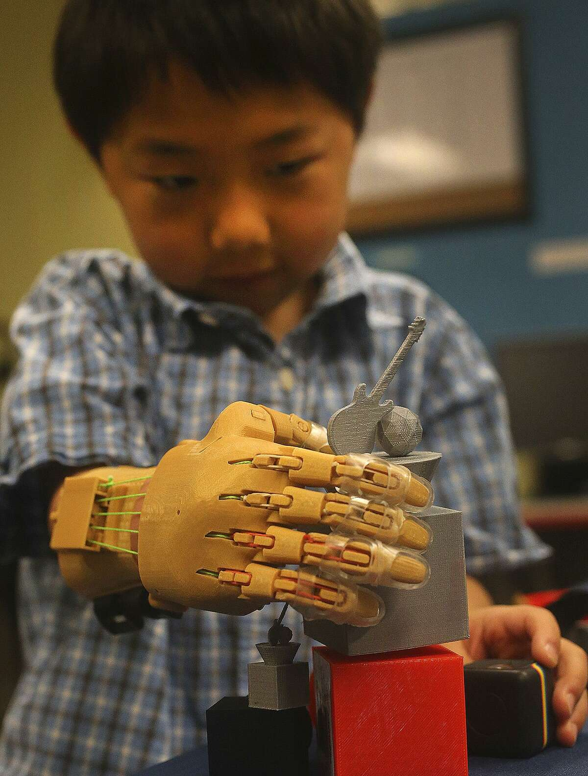 Zack Robbins,6, uses a prosthetic hand Wednesday March 8, 2017 made with a 3D printer by School of Science and Technology student Justin Cantu,16. Robbins was born with underdeveloped right hand and Cantu used technology created by an on-line community called e-NABLE to make the hand for Robbins.