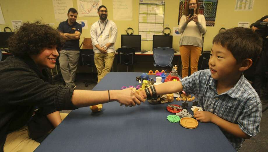 Zack Robbins,6, (right) uses a prosthetic hand Wednesday March 8, 2017 to shake hands with School of Science and Technology student Justin Cantu,16 (left). Robbins was born with underdeveloped right hand and Cantu used technology created by an on-line community called e-NABLE to make the hand for Robbins with a 3D printer. Photo: John Davenport, Staff / San Antonio Express-News / ©San Antonio Express-News/John Davenport