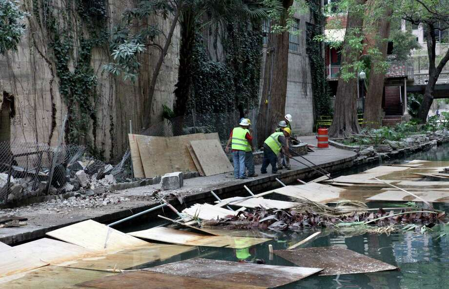 Members of the demolition team try to retrieve material used to protect pedestrians walking along River Walk Thursday evening after a small portion of a wall collapsed onto the protective covering.  The wall was part of the Solo Serve building which is being demolished to make way for a new structure. Photo: Juanito Garza/Staff / San Antonio Express-News
