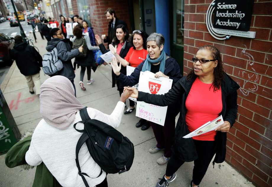 "Teacher Pia Martin greets students as they arrive to school at the Science Leadership Academy as teachers take part in ""A Day Without a Woman"" demonstration in Philadelphia, Wednesday, March 8, 2017. Organizers of January's Women's March are calling on women to stay home from work and not spend money in stores or online to show their impact on American society. (AP Photo/Matt Rourke) Photo: Matt Rourke, STF / Copyright 2017 The Associated Press. All rights reserved."