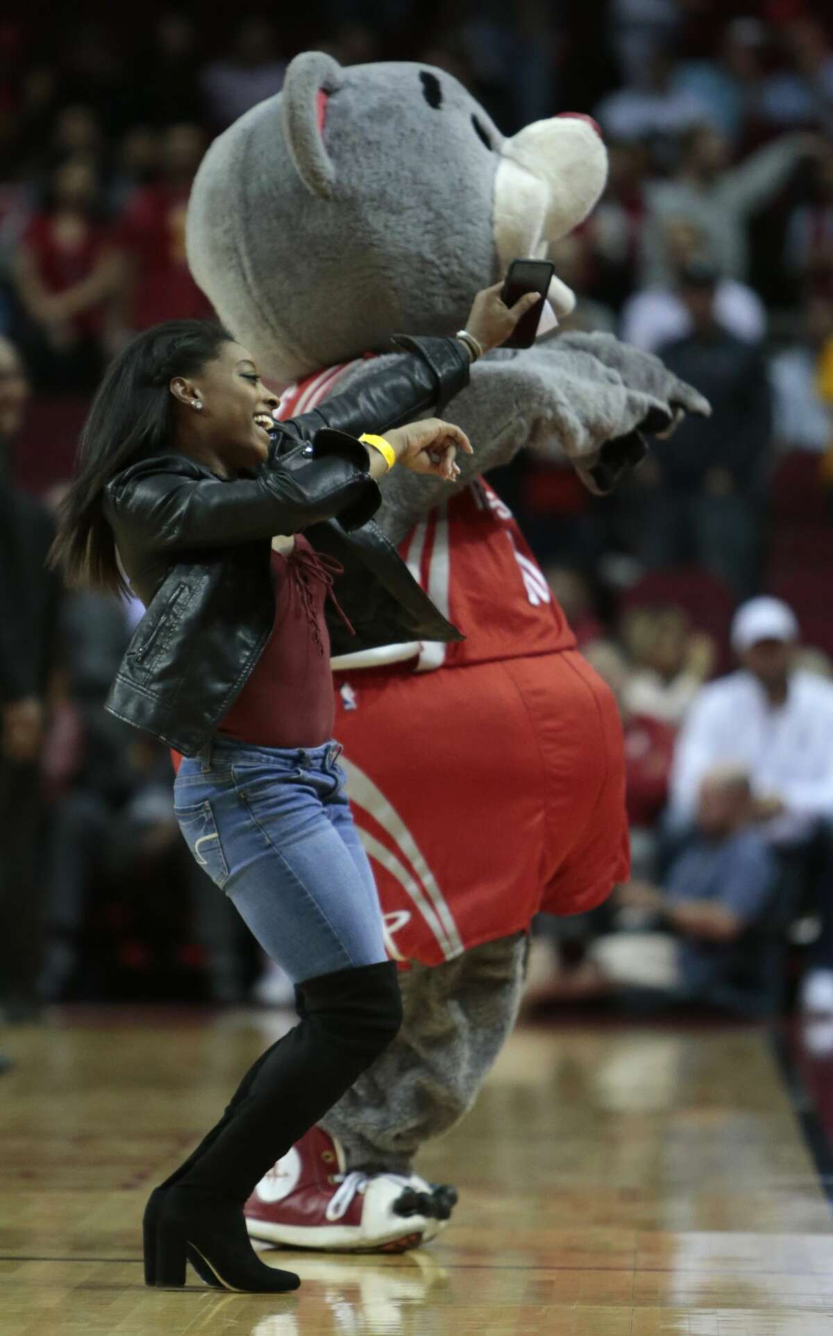 Olympic gold medalist Simone Biles, left, dances with Houston Rockets mascot Clutch during a time out in the fourth quarter of an NBA basketball game between the Rockets and the Utah Jazz at Toyota Center on Wednesday, March 8, 2017, in Houston. ( Brett Coomer / Houston Chronicle )