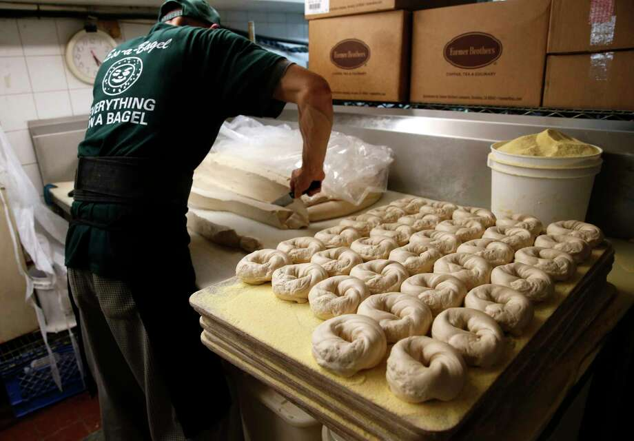 Sam Ung cuts through bagel dough at Ess-a-Bagel in New York. A private survey indicates that hiring across the U.S. could be accelerating.  Photo: Kathy Willens, STF / Copyright 2016 The Associated Press. All rights reserved. This material may not be published, broadcast, rewritten or redistribu