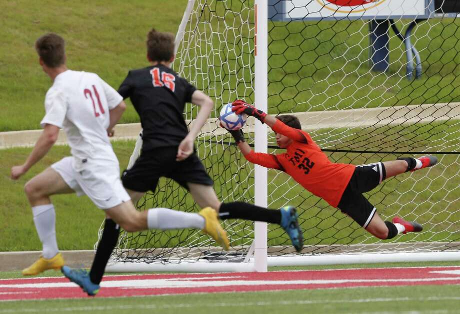 TMI-Episcopal goal keeper Santiago Vigil safes a goal and defending  TMI-Episcopal Defense Liam Morehead (16)   from Grapevine Faith Christian player, during the second half of a High School Soccer TAPPS Division II State Championship on March 8, 2017 at WACO ISD stadium, in Waco, Texas. TMI won 3-1. Jose Yau/Special Contributor Photo: Jose Yau / Jose's Photography 2017