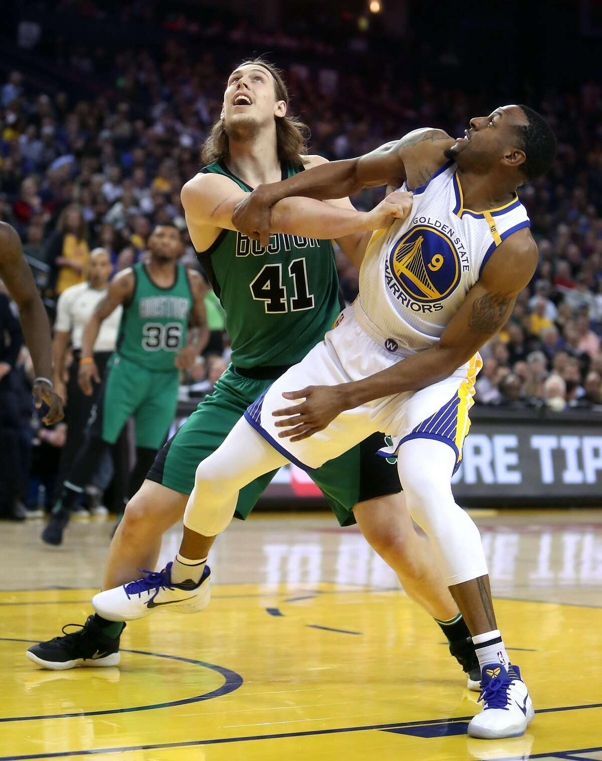 Golden State Warriors' Andre Iguodala and Boston Celtics' Kelly Olynyk battle for rebound position in 2nd quarter during NBA game at Oracle Arena in Oakland, Calif., on Wednesday, March 8, 2017.