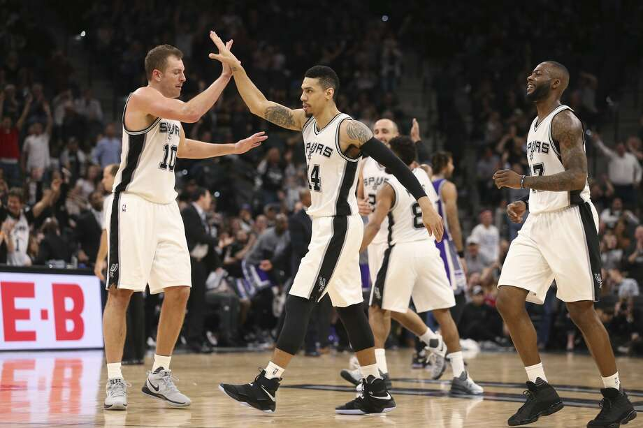 San Antonio Spurs' Danny Green gets a high five from David Lee after scoring a late fourth quarter three-pointer against the Sacramento Kings at the AT&T Center, Wednesday, March 8, 2017. The Spurs won 114-104. On the right is Jonathon Simmons. Photo: JERRY LARA/San Antonio Express-News