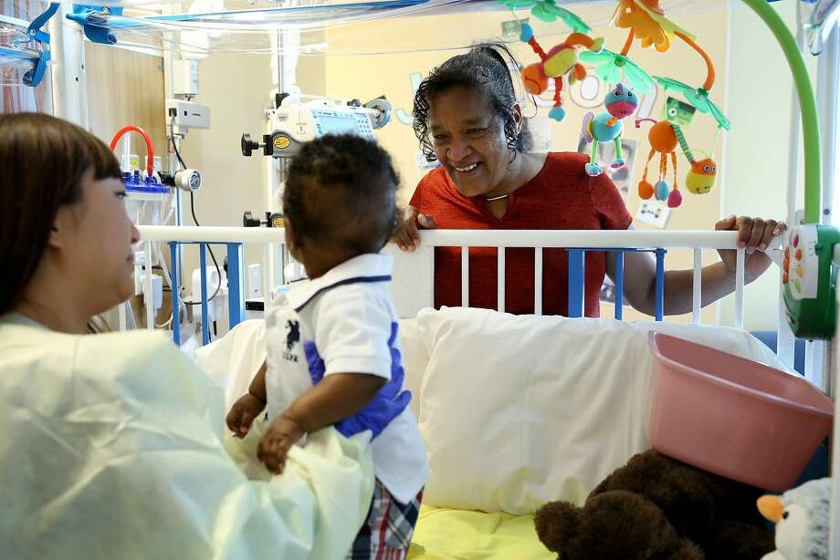 From right: Dannie Hawkins checks on her nephew Ja'Ceon Golden, who is being held by patient care assistant Grace Deng at UCSF Benioff Children's Hospital on Wednesday, March 8, 2017, in San Francisco, Calif. Golden, who is five months old, is diagnosed with severe combined immunodeficiency disease (SCID). He is a patient at UCSF, where he stays in a sterile room. The hospital is working on a new gene therapy treatment for SCID. Hawkins brought her nephew Golden from New Mexico for the experimental treatment. Photo: Santiago Mejia, The Chronicle