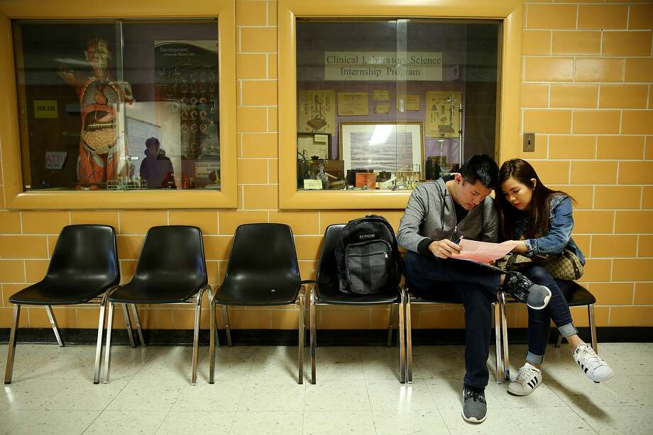 Stephanie Barria and husband Denz fill out a form before entering the Volunteer Income Tax Assistance program. Photo: Santiago Mejia, The Chronicle