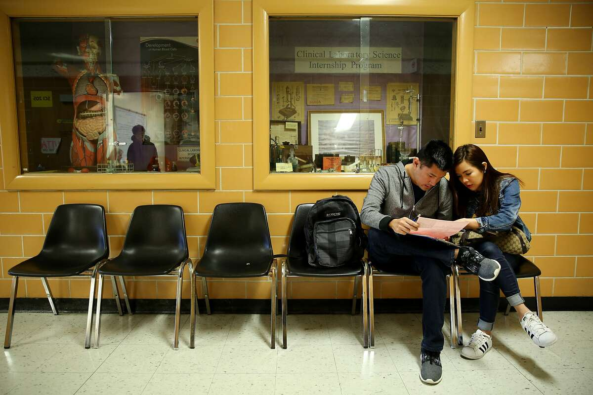 From right: Stephanie Barria and her husband Denz fill out a form before entering VITA at San Francisco State University on Wednesday, March 8, 2017, in San Francisco, Calif. The IRS offers a Volunteer Income Tax Assistance (VITA) program, where volunteers help with tax returns for free to people who generally make $54,000 or less.