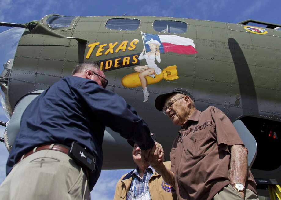 Wayne Kennedy, with the Commemorative Air Force, hands World War II veterans Curtis Blair and R.B Kelley challenge coins during a welcoming ceremony for a B-17 Flying Fortress, known as 'Texas Raiders,' at the General Aviation Services on the north side of Conroe-North Houston Regional Airport Wednesday, March 8, 2017, in Conroe. The heavy-bomber, maintained and operated by the Commemorative Air Force Gulf Coast Wing, initially flew out of David Wayne Hooks Memorial Airport, but will now call the Montgomery County airport home. Photo: Jason Fochtman, Staff Photographer / Houston Chronicle / © 2017 Houston Chronicle