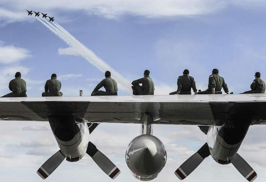(for PhotoNight by Elizabeth Conley) Members of the U.S. Coast Guard sit on the wing of their Lockheed HC-130H Hercules, as they watch the Blue Angles perform during  Wings Over Houston Air Show at Ellington Airport on  Sunday, Oct. 23, 2016, in Houston. Photo: Elizabeth Conley, Staff / Houston Chronicle / © 2016 Houston Chronicle