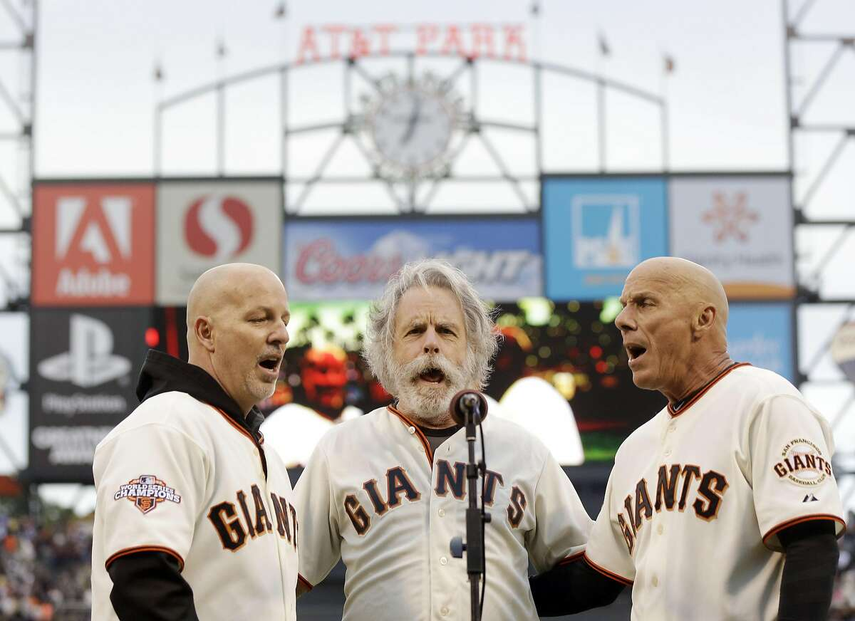 On Aug. 5, 2013 photo, San Francisco Giants third base coach Tim Flannery, right, and his brother Tom, left, sing the national anthem with Bob Weir of the Grateful Dead before a baseball game against the Milwaukee Brewers in San Francisco. (AP Photo/Marcio Jose Sanchez, file)