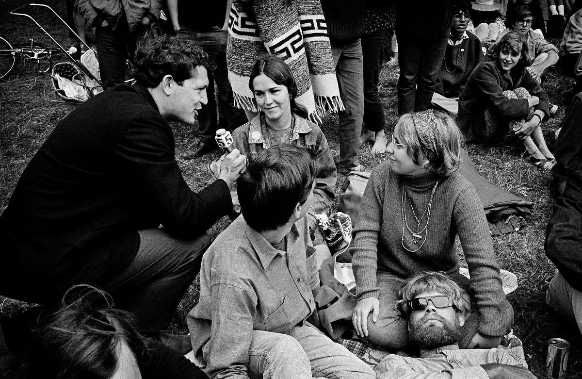 A reporter interviews concert goers during a Jefferson Airplane/Grateful Dead Concert in Golden Gate Park 1967.