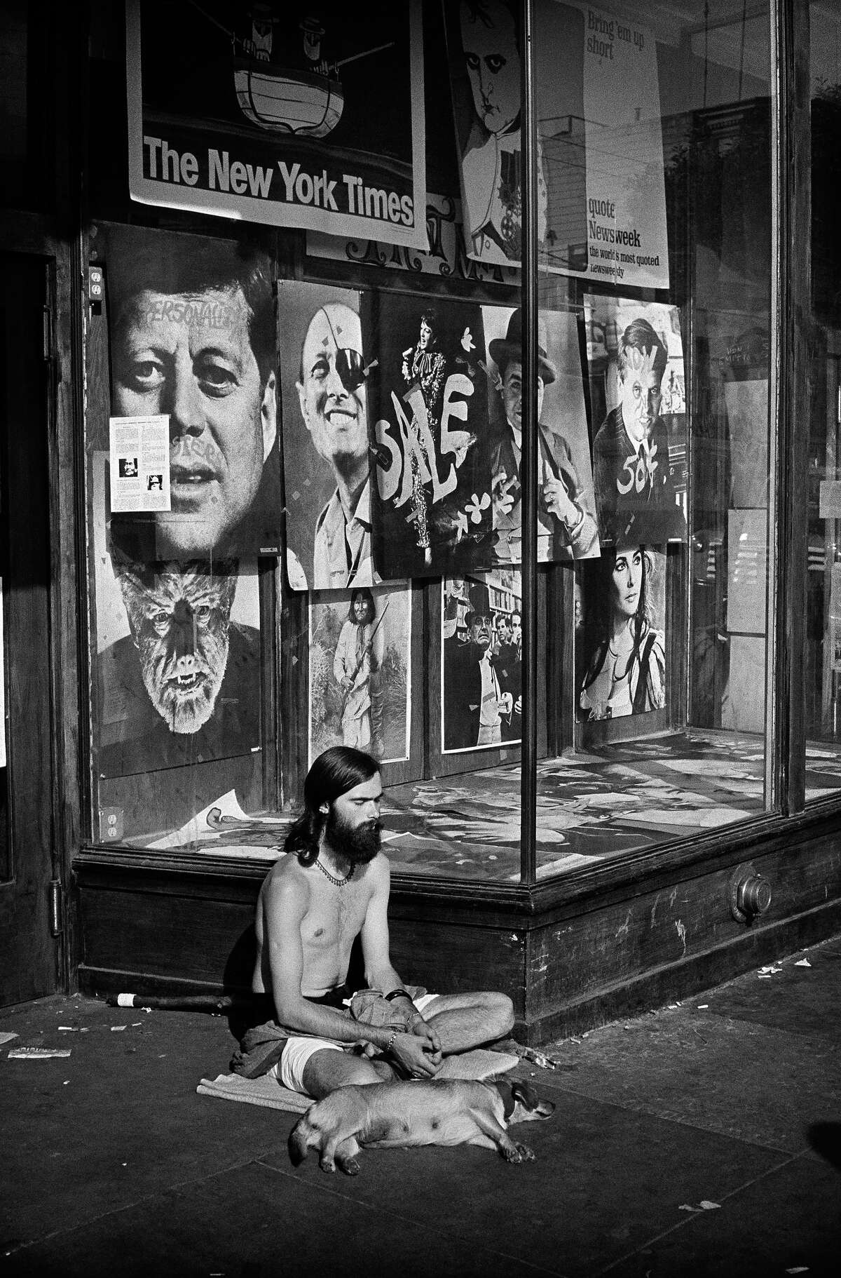 A man and his dog are seen in the doorway of a poster shop on Haight St. in 1967.