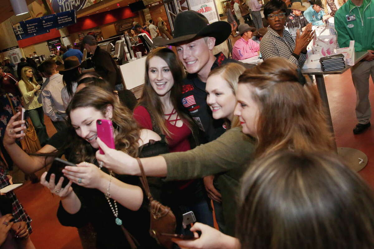 Tie-down roper Tuf Cooper is surrounded by a group of fans and was asked for selfies while leaving the fan zone after his Houston Livestock Show and Rodeo Super Series 1 Round 2 competition at NRG Stadium Wednesday, March 8, 2017, in Houston.