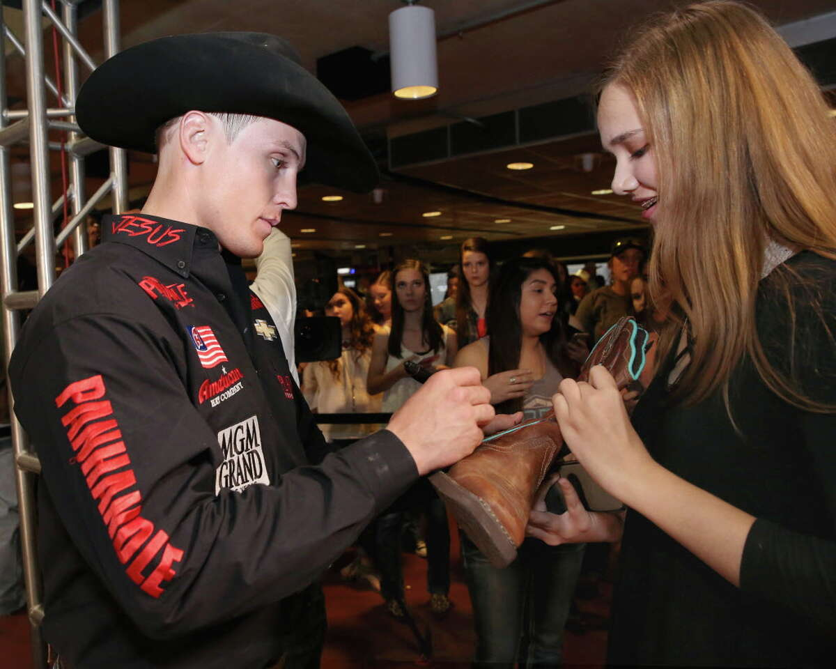 Tie-down roper Tuf Cooper signs Madison Sears' boot at the fan zone after his Houston Livestock Show and Rodeo Super Series 1 Round 2 competition at NRG Stadium Wednesday, March 8, 2017, in Houston.