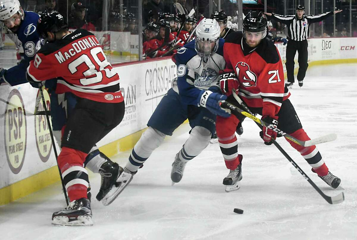 Albany Devils' Kevin Rooney, right, and Syracuse Crunch's Brian Hart battle for the puck during a hockey game at the Times Union Center on Wednesday, Jan. 18, 2017 in Albany, N.Y. Devils' Jacob MacDonald checks Crunch's PL Letourneau-Leblond at left. (Lori Van Buren / Times Union) ORG XMIT: MER2017011821281685