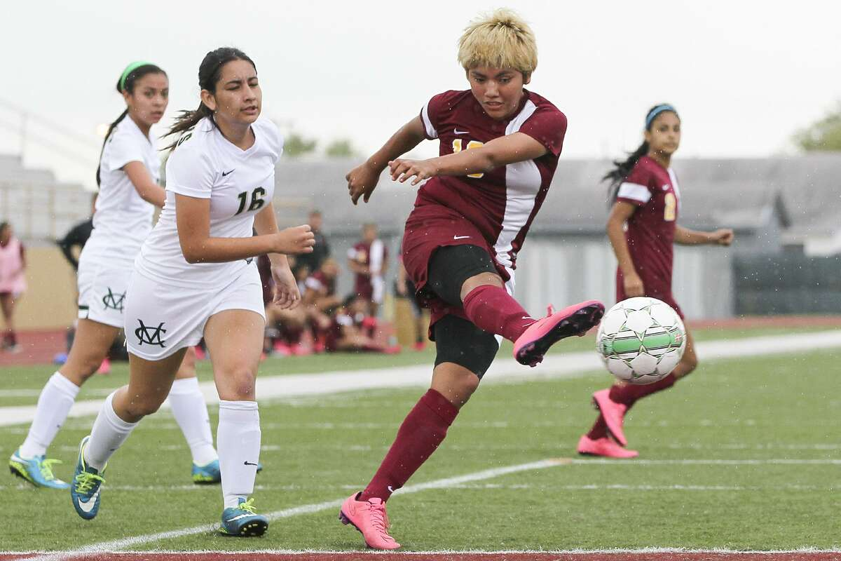 Harlandale's Jazmin Baltazar takes a shot at the goal as McCollum's Joana Villarreal (16) gives chase during their District 28-5A game at Harlandale Memorial Stadium on Thursday, March 17, 2016. Baltazar scored four goals to lead Harlandale past McCollum 6-0. MARVIN PFEIFFER/ mpfeiffer@express-news.net