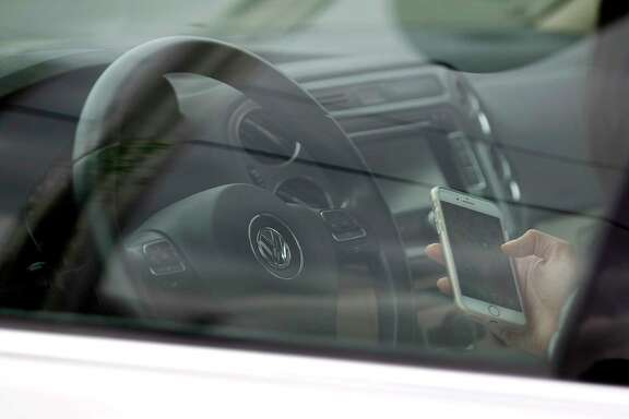 A woman text as she drives along Westheimer near The Galleria on March 9.