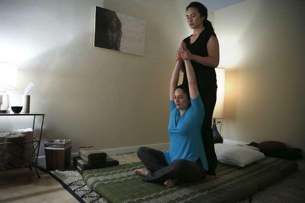 Upuia Ahkiong of Kua Body Studios stands as she gives massage therapist Jennifer Y. Ruiz a Thai massage in Los Altos.
