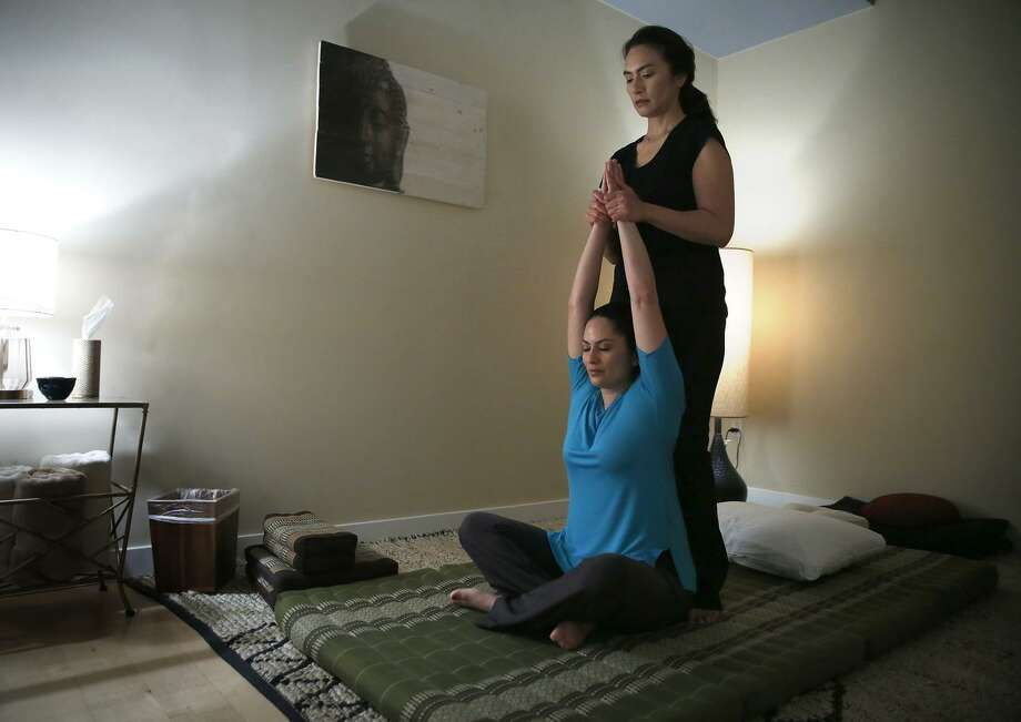 Upuia Ahkiong of Kua Body Studios stands as she gives massage therapist Jennifer Y. Ruiz a Thai massage in Los Altos. Photo: Liz Hafalia / The Chronicle / online_yes