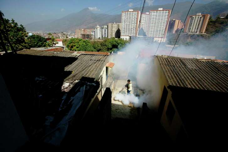FILE - In this Monday, Feb. 1, 2016 file photo, a Sucre municipality worker fumigates for Aedes aegypti mosquitoes that transmit the Zika virus in the Petare neighborhood of Caracas, Venezuela. Ahead of the annual American College of Cardiology conference in Washington in March 2017, doctors say they have tied infection with the Zika virus to possible new heart problems in adults. The evidence is only in eight people in Venezuela and does not prove a link. It's too soon to know how often this might be happening, although it seems less common than the troubles the mosquito-borne virus has been causing for pregnant women and their fetuses. (AP Photo/Fernando Llano)
