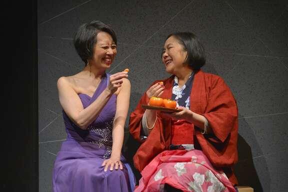 "Sisters Natsuko (Jeanne Sakata) and Noriko (Emily Kuroda) share a persimmon in�TheatreWorks' ""Calligraphy."""