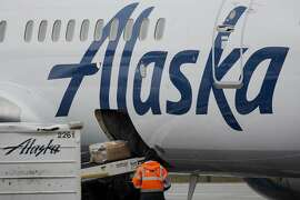 A worker watches baggage as it enters an Alaska Air Group Inc. jet at Seattle-Tacoma International (SEA) airport in Seattle, Washington, U.S., on Friday, Feb. 3, 2017. Alaska Air is expected to release earnings figures on February 8. Photographer: David Ryder/Bloomberg