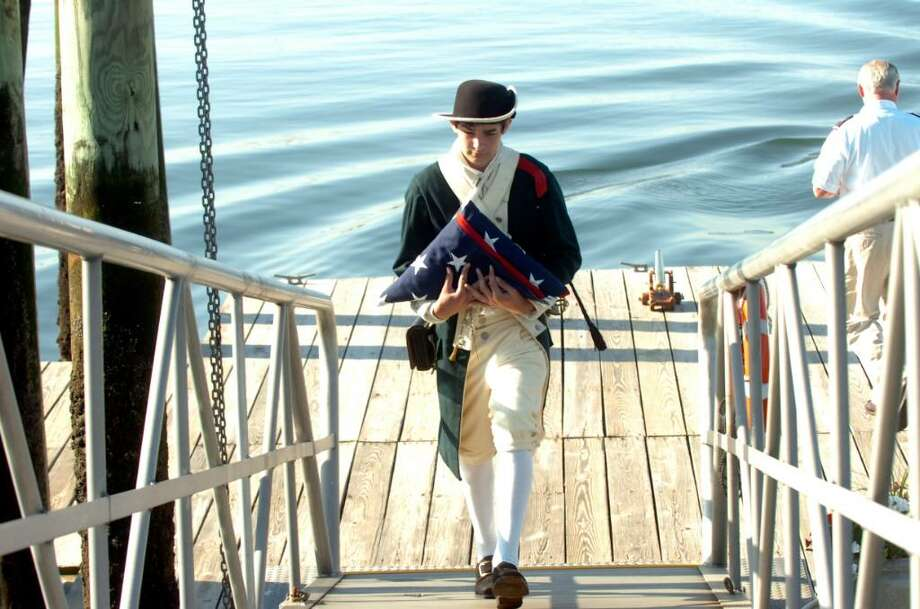 Jonathan Hughes, 15, dressed in colonial garb carries the American Flag at the dockside Memorial Day ceremony at the Indian Yacht Club on Monday, May 31, 2010. Photo: Helen Neafsey / Greenwich Time