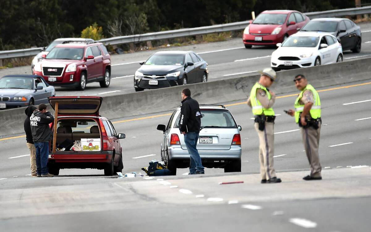 Police investigate as a van (R) with shattered glass and bullet holes (L) is seen alongside another vehicle (L) on northbound Interstate 80 after unknown assailants shot at a driver and passenger in Richmond, California on March 09, 2017.