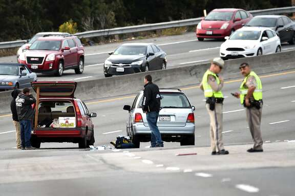 Police investigate as a van (R) with shattered glass and bullet holes (L) is seen alongside another vehicle (L) on northbound Interstate 80 after unknown assailants shot at a driver and passenger in Richmond, California on March 09, 2017. The victims are currently in critical condition and the suspects are still at large.