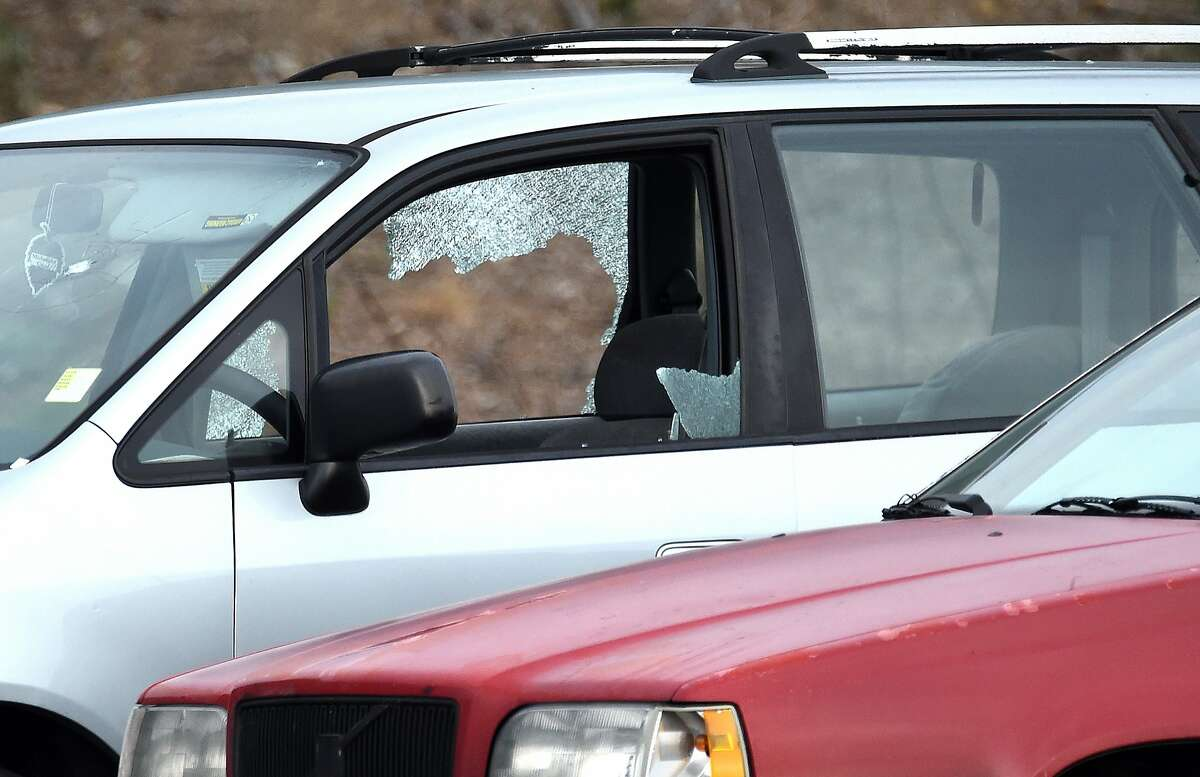 Police investigate as a van with shattered glass and bullet holes (L) is seen alongside another vehicle (R) on northbound Interstate 80 after unknown assailants shot at a driver and passenger in Richmond, California on March 09, 2017.