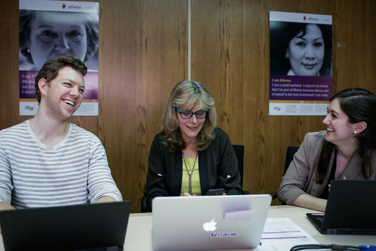 Dr. Laura Esserman (center) laughs during a phone call as she works with researchers Kenny Wimmer (left) and Roxanna Firouzian (right) in San Francisco, California, on Thursday, March 9, 2017.