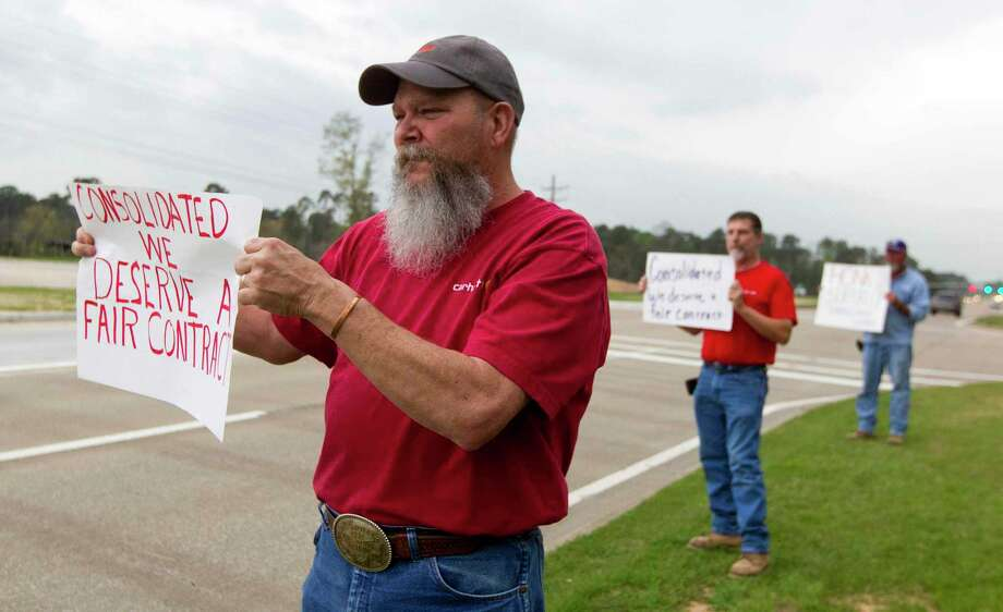 Kenny Kilgore holds a sign as he joins fellow union employees with Communications Workers of America Local 6218 on a picket line in front of the Consolidated Communication's building on Loop 336 West Thursday, March 9, 2017, in Conroe. The company and the union have been negotiating the employees contract as a part of a three-year renewal since September. The union employees are concerned about contract changes that include insurance cost increase with a raise that will not offset the cost and the elimination of retirement benefits. Photo: Jason Fochtman, Staff Photographer / © 2017 Houston Chronicle