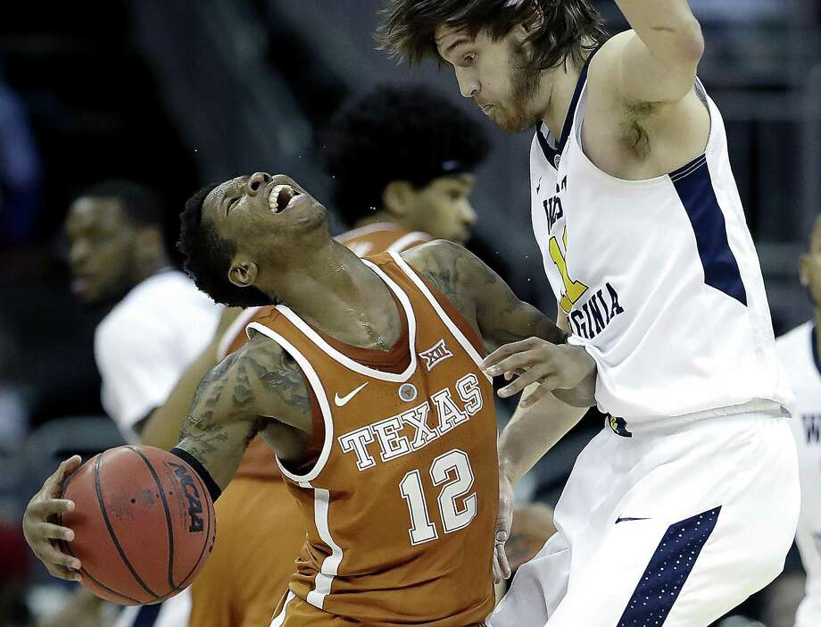 Texas' Kerwin Roach Jr. (12) collides with West Virginia's Nathan Adrian during the second half of an NCAA college basketball game in the quarterfinal round of the Big 12 tournament in Kansas City, Mo., Thursday, March 9, 2017. (AP Photo/Charlie Riedel) Photo: Charlie Riedel, STF / Associated Press / Copyright 2017 The Associated Press. All rights reserved.