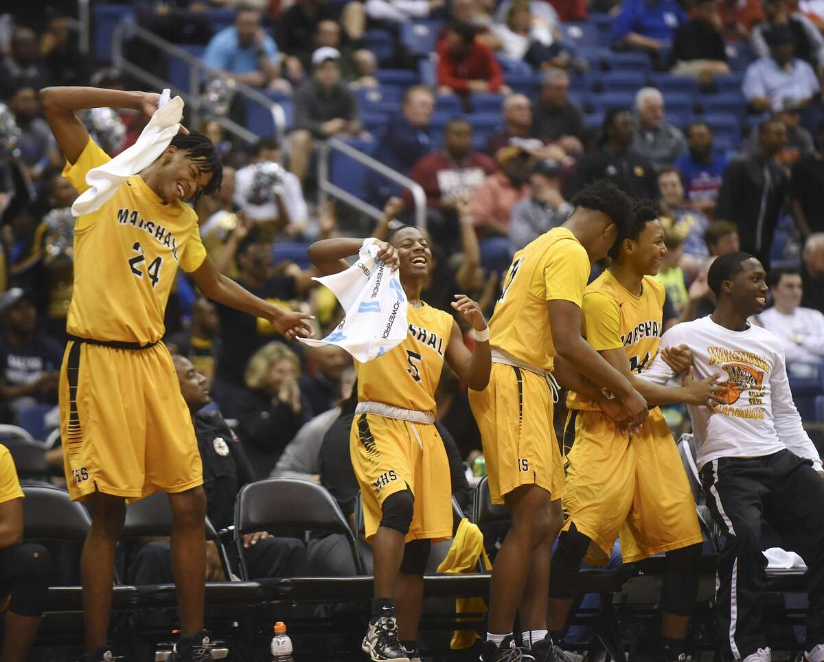 John Walker III (24), Anthony Norman and others on the Fort Bend Marshall bench celebrate as time winds down on their victory over Northwest in Class 5A state semifinals action in the Alamodome on Thursday, March 9, 2017.