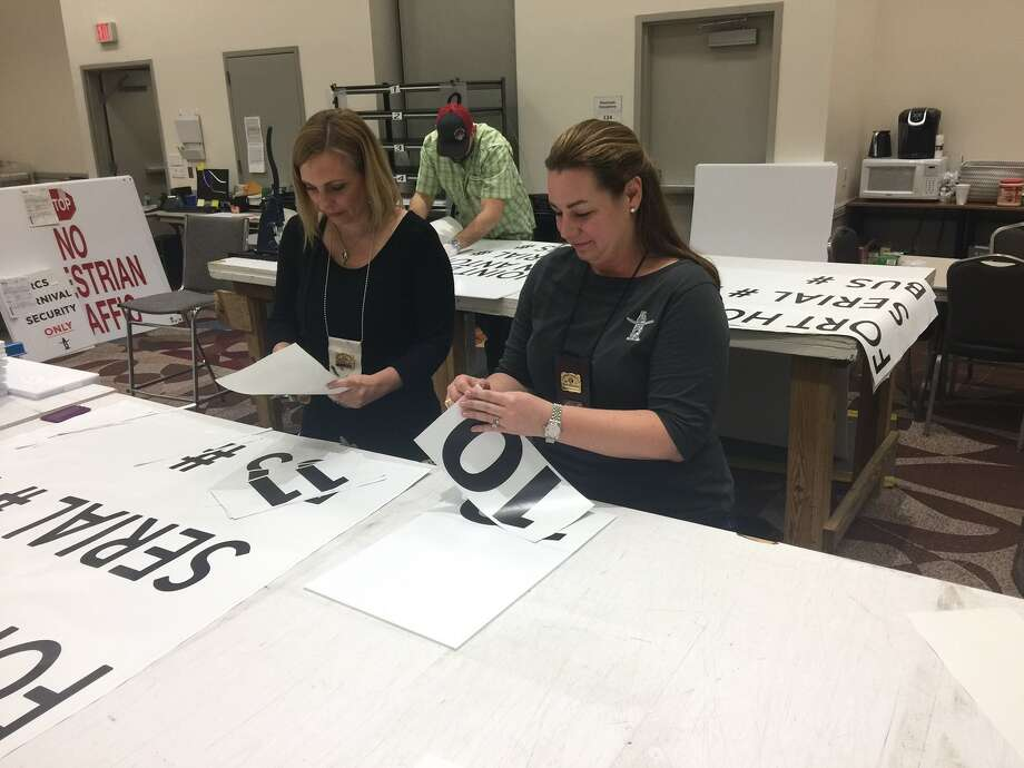 Kristy Broughton (left) and Chastity DeVito (right) of the Graphics and Signage Committee preparing signs for the arrival of troops from Fort Hood for Armed Forces Appreciation Day. Photo: Mike Glenn, Houston Chronicle