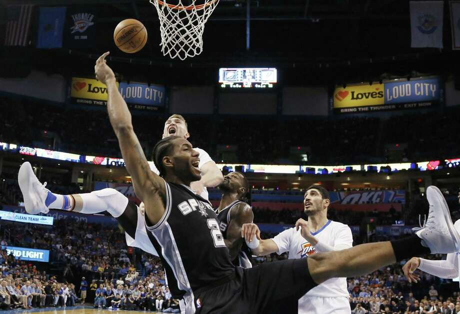San Antonio Spurs forward Kawhi Leonard (2) loses the ball after a foul by Oklahoma City Thunder forward Domantas Sabonis, left rear, during the second quarter of an NBA basketball game in Oklahoma City, Thursday, March 9, 2017. Thunder center Enes Kanter is at right. (AP Photo/Sue Ogrocki) Photo: Sue Ogrocki, STF / Associated Press / AP2017