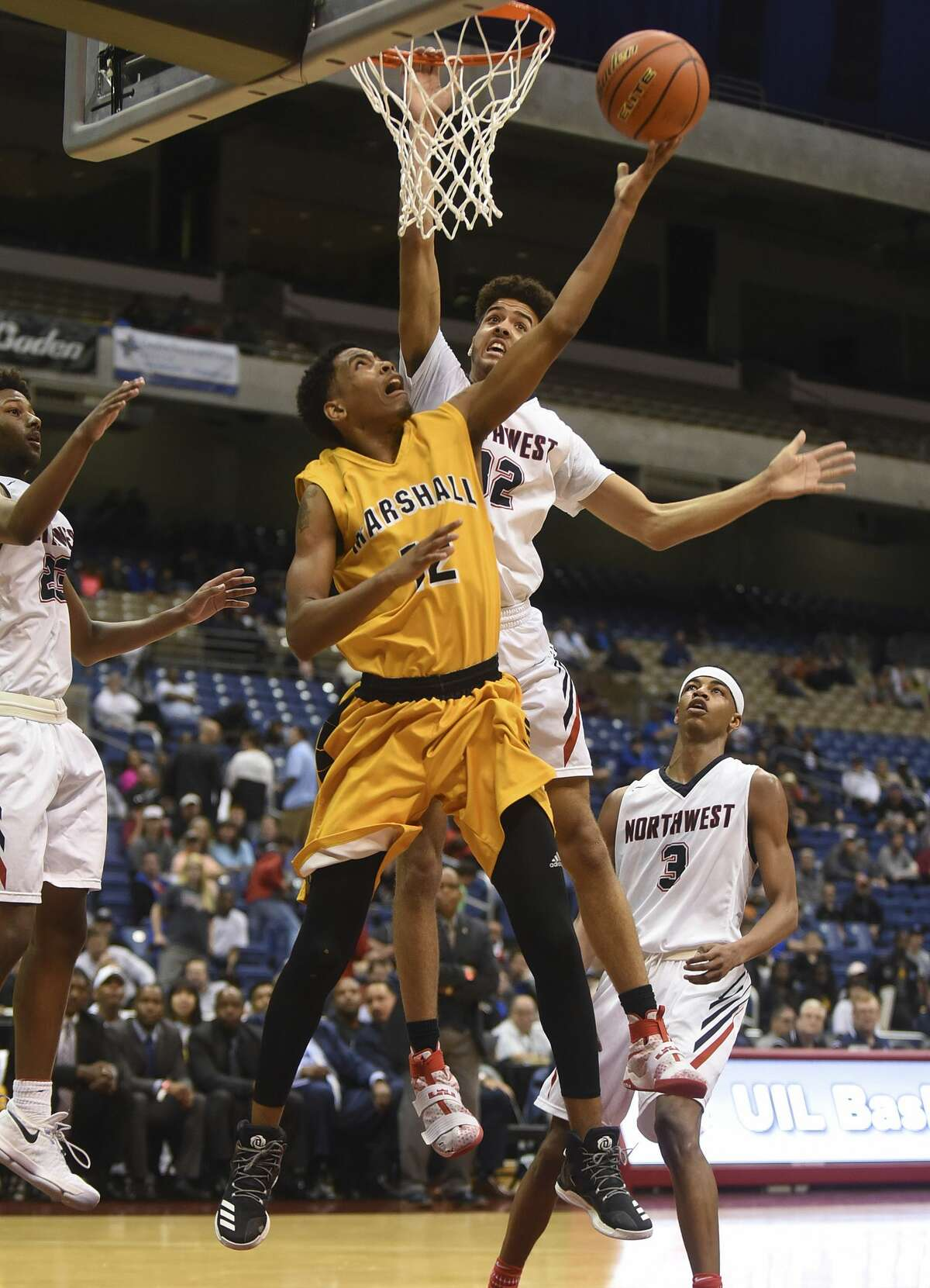 Tajzmel Sherman of Fort Bend Marshall shoots a reverse layup as Jay Am'Mons of Northwest defends during second-half Class 5A state semifinals action in the Alamodome on Thursday, March 9, 2017.